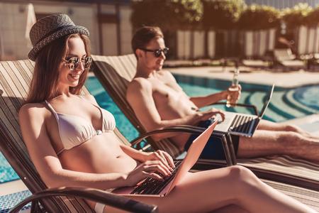 休暇にも取り組んでいます!サングラスの若いカップルは、ラップトップとスイミング プールのそばの長いすに横たわっています。