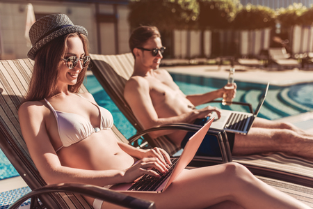 Working even on vacation! Young couple in sunglasses are lying on a chaise-longues near swimming pool with laptops.