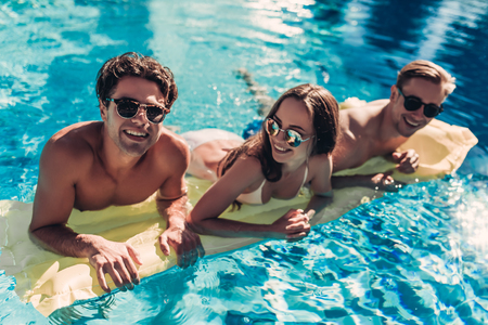 Happy attractive young friends in sunglasses are having fun in swimming pool on an inflatable mattress and smiling 版權商用圖片