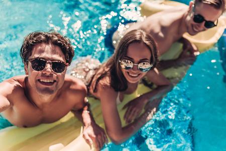선글라스에 행복 한 매력적인 젊은 친구는 부 풀은 매트리스에 수영장에서 재미 있고 selfie 만들기 동안 웃 고있다. 스톡 콘텐츠
