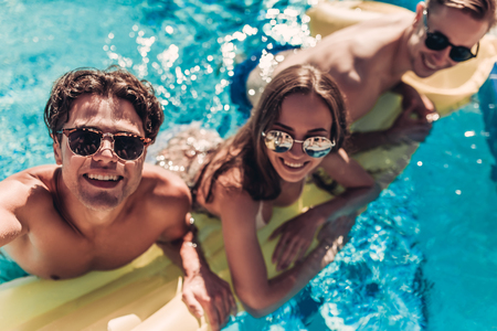 Happy attractive young friends in sunglasses are having fun in swimming pool on an inflatable mattress and smiling while making selfie. Stock Photo