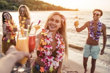 ¡Aclamaciones! Grupo de amigos atractivos jóvenes están teniendo diversión en la playa, bebiendo los cocteles y sonriendo. Partido en estilo hawaiano.
