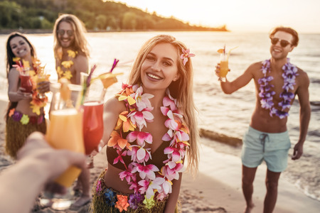 Cheers! Group of young attractive friends are having fun on beach, drinking cocktails and smiling. Party in Hawaiian style.