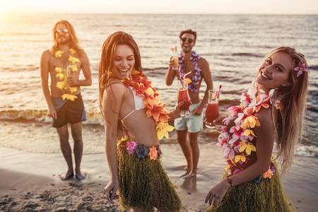 Group of young attractive friends are having fun on beach, drinking cocktails, dancing and smiling. Party in Hawaiian style.