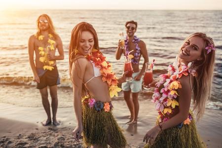 Gruppo di giovani amici attraenti si divertono sulla spiaggia, bevendo cocktail, ballando e sorridendo. Festa in stile hawaiano. Archivio Fotografico - 83496205