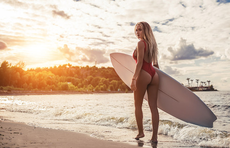 Attractive sexy young woman in red swimsuit is standing on beach with white surfboard in hands.