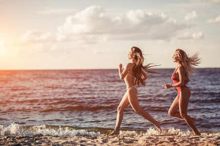 Two beautiful girls are running and having fun on beach in swimsuits.