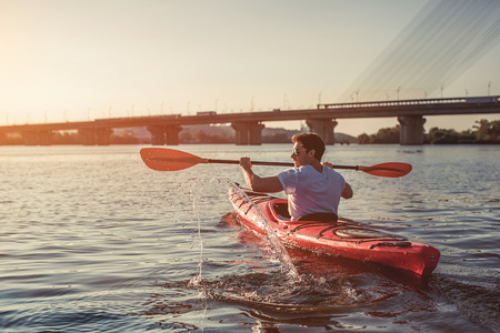 잘 생긴 스포티 한 남자 강에서 석양에 카약. 혼자 카누. 스톡 콘텐츠