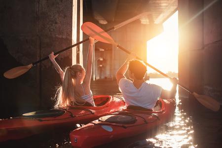 아름 다운 젊은 부부는 강에서 카약입니다. 일몰을 기다리는 중입니다. 함께 카누 타기