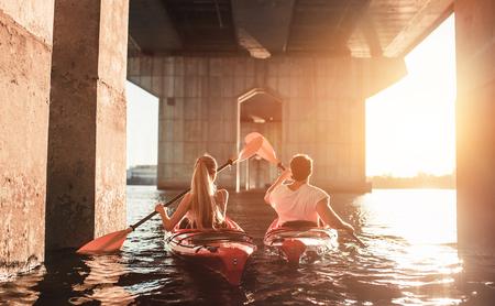 Schöne junge Paar ist Kajak auf Fluss. Warten auf den Sonnenuntergang. Kanufahren zusammen Lizenzfreie Bilder