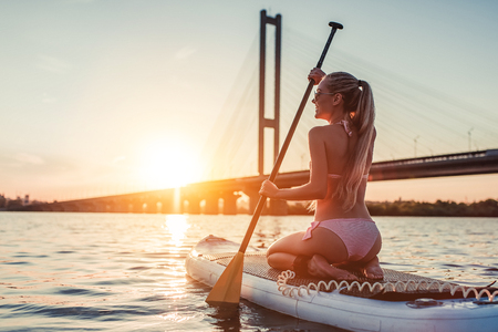 Woman on stand up paddle board. Having fun on SUP board during sunset. Active lifestyle.