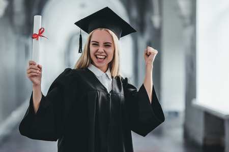 Excited happy female student graduate is standing in university hall in mantle with diploma in hand, smiling and looking at the camera. Stok Fotoğraf