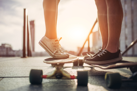Cropped image of young couple is standing face to face to each other on longboards outdoors. Teenagers with skateboards in the city. Фото со стока