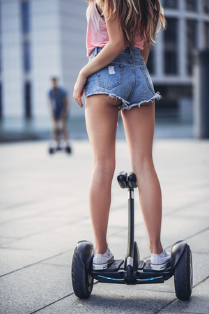Het gelukkige tienerpaar heeft pret in de stad. Jonge man en vrouw op gyroscooters. Stockfoto