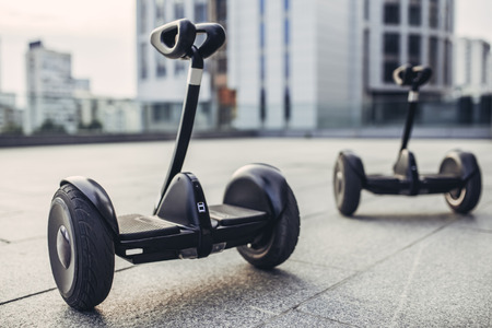 Two gyro scooters are standing on the street. Couple of gyro scooters in the background of city. Banco de Imagens