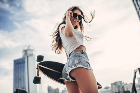 Young woman is posing with skateboard in the city. Female teenager outdoor with longboard. Stockfoto