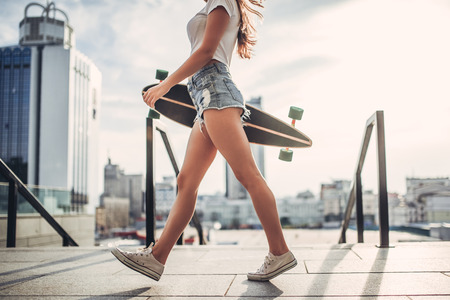 Cropped image of young woman is posing with skateboard in the city. Female teenager outdoor with longboard.