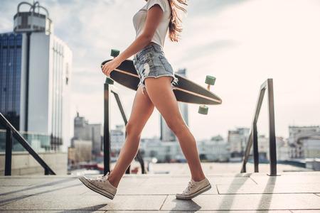Image recadrée de jeune femme pose avec skateboard dans la ville. Adolescente en plein air avec longboard. Banque d'images - 84368625