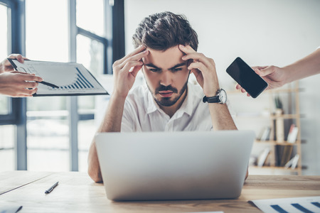 El hombre de negocios joven del trastorno está trabajando en oficina ligera moderna bajo tensión. Sensación de cansancio
