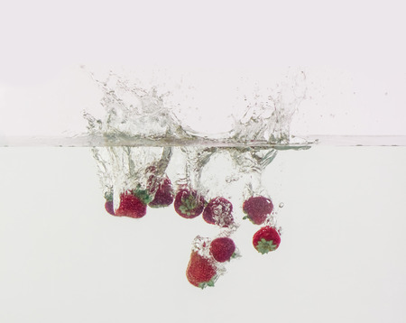 Berries are thrown into the water in transparent vessel. Strawberries and water splash on white background.