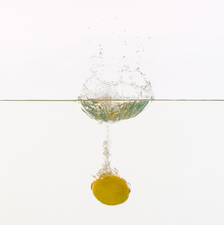 Fruits are thrown into the water in transparent vessel. Lemon and water splash on white background. Stock Photo