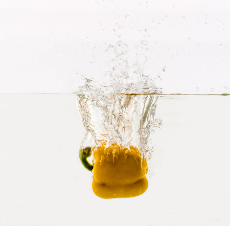 Vegetables are thrown into the water in transparent vessel. Yellow Bulgarian pepper and water splash on white background.