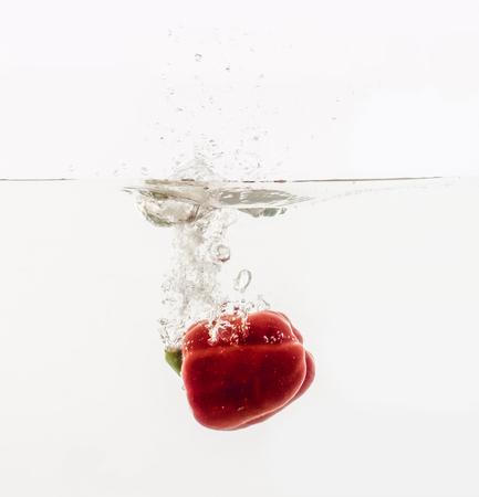 野菜は透明な容器の中で水に投げ込まれる。赤いブルガリアのコショウと白い背景に水のスプラッシュ。