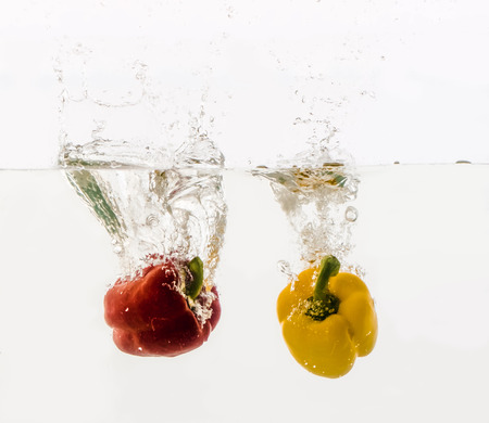 Vegetables are thrown into the water in transparent vessel. Red and yellow Bulgarian peppers with water splash on white background.