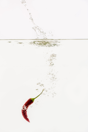 Vegetables are thrown into the water in transparent vessel. Hot pepper and water splash on white background.