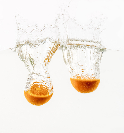 Fruits are thrown into the water in transparent vessel. Cut orange and water splash on white background.