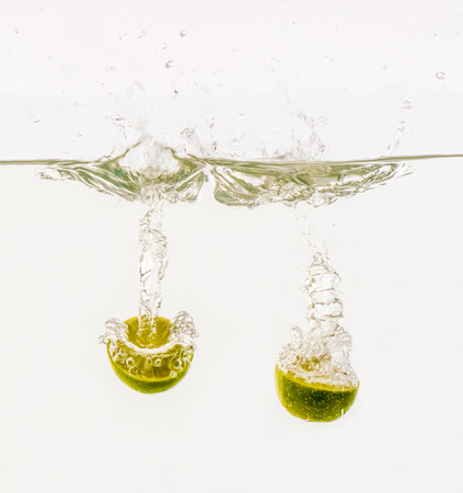 Fruits are thrown into the water in transparent vessel. Cut lime and water splash on white background.