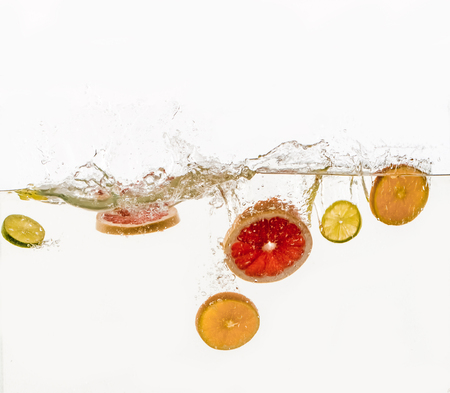 Cut fruits are thrown into the water in transparent vessel. Orange, lime, grapefruit and water splash on white background.