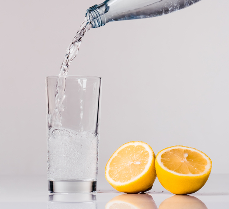 Flow of water is pouring into the glass on white background. Cut lemon is lying nearby. Isolated lemon water.