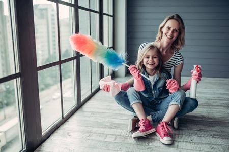 美しい若い女性と彼女の少し陽気な娘は、自宅で掃除をしながら楽しんでいます。清掃用具と笑顔します。 写真素材