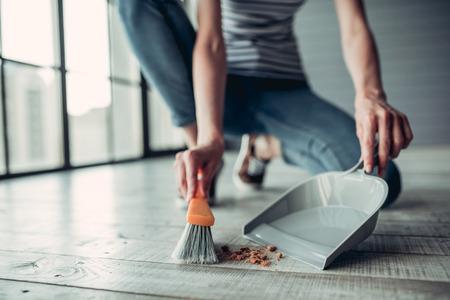 Het bebouwde beeld van mooie jonge vrouw houdt schoonmakende hulpmiddelen en doet thuis schoonmakend.