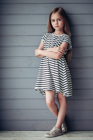 Full-lenght image of charming little girl with long hair is standing on a grey background and posing