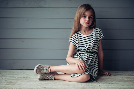 Charming little girl is sitting on the floor on grey background with perceptive glance. Cute girl posing Stockfoto
