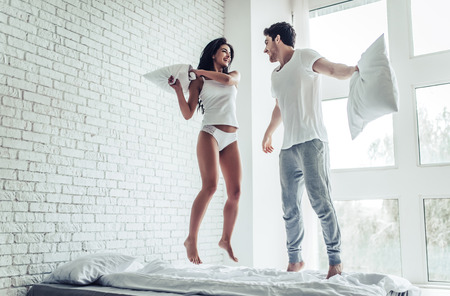Happy young couple is having fun in bedroom. Enjoying the company of each other. Jumping on bed while having pillow battle