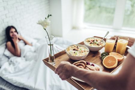 ¡Buenos días! Desayuno saludable en la cama. Joven y bella mujer está acostado en la cama mientras su hombre guapo traer el desayuno sabroso.