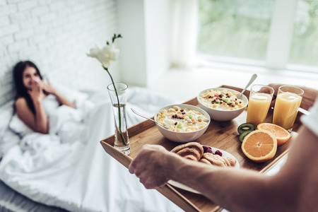 Good morning! Healthy breakfast in bed. Beautiful young woman is lying in bed while her handsome man bringing tasty breakfast. Фото со стока - 85849463