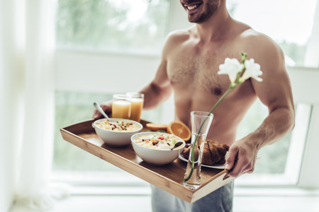 Good morning! Cropped image of handsome sporty man is standing with healthy breakfast in hands.