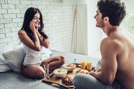 Good morning! Healthy breakfast in bed. Young beautiful love couple is sitting in bed before having breakfast. Banque d'images