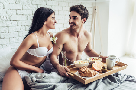 Good morning! Handsome man brings healthy breakfast in bed. Young beautiful love couple is sitting in bed before having breakfast.