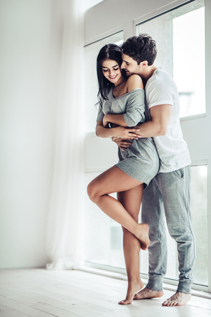 Full-length image of young beautiful couple is enjoying the company of each other at home. Hugging and kissing. Banque d'images