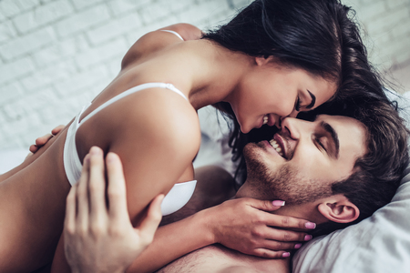 Happy couple is lying in bed together. Enjoying the company of each other. Banque d'images