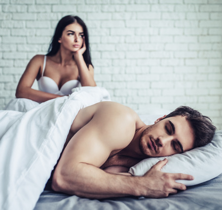 Couple is having problems in bed. Beautiful young upset woman is sitting on bed while her handsome man is sleeping.