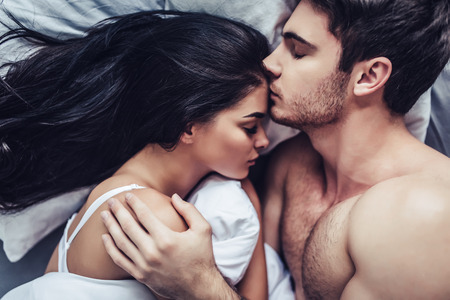 Close-up of happy couple is lying in bed together. Enjoying the company of each other.