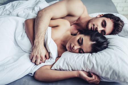 Happy couple is lying in bed. Enjoying the company of each other. Sleeping together.