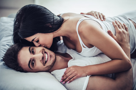 Happy couple is lying in bed together. Enjoying the company of each other. Young woman is kissing her handsome man. Banque d'images