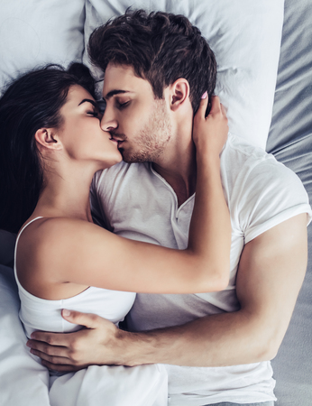 Happy couple is lying in bed together. Kissing and enjoying the company of each other. Banque d'images